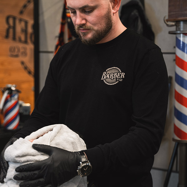 Grant at Barber & Co giving a client a hot towel shave